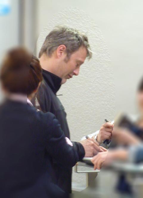 空港でファンにサインをするミケルセン