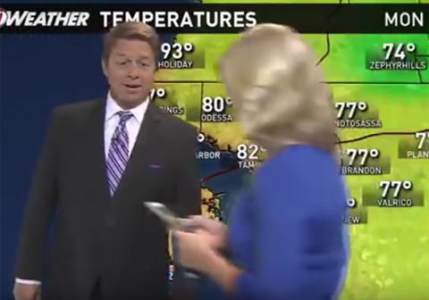 天気予報中に携帯を持ちながらカメラの前を横切る女性キャスター