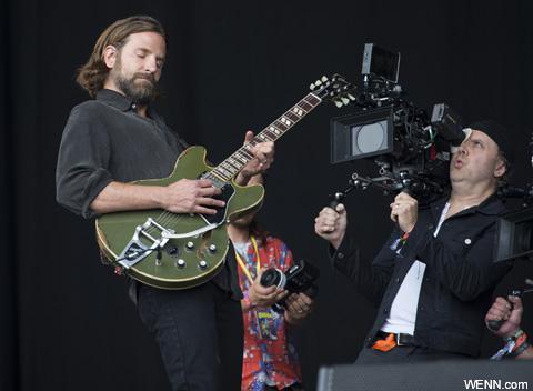 グラストンベリーのステージ上で撮影をするブラッドリー・クーパー
