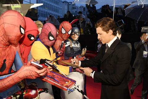 スパイダーマンの仮装をしたファンにファンサービスをするトム